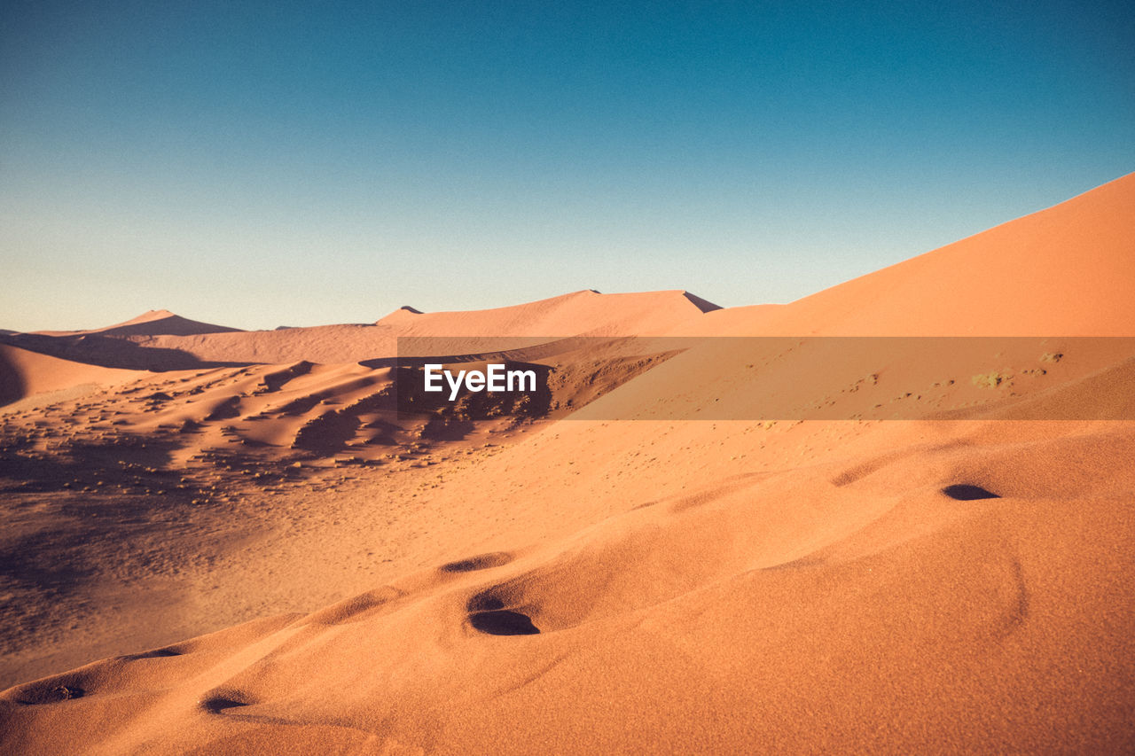 SCENIC VIEW OF SAND DUNES AGAINST CLEAR BLUE SKY