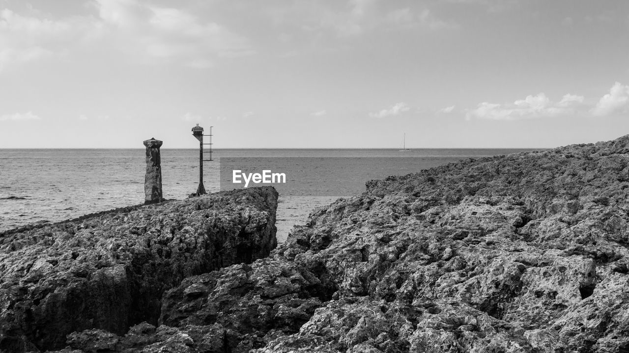 sea, water, horizon over water, tranquility, tranquil scene, scenics, sky, beauty in nature, nature, day, rock - object, lighthouse, no people, outdoors, groyne