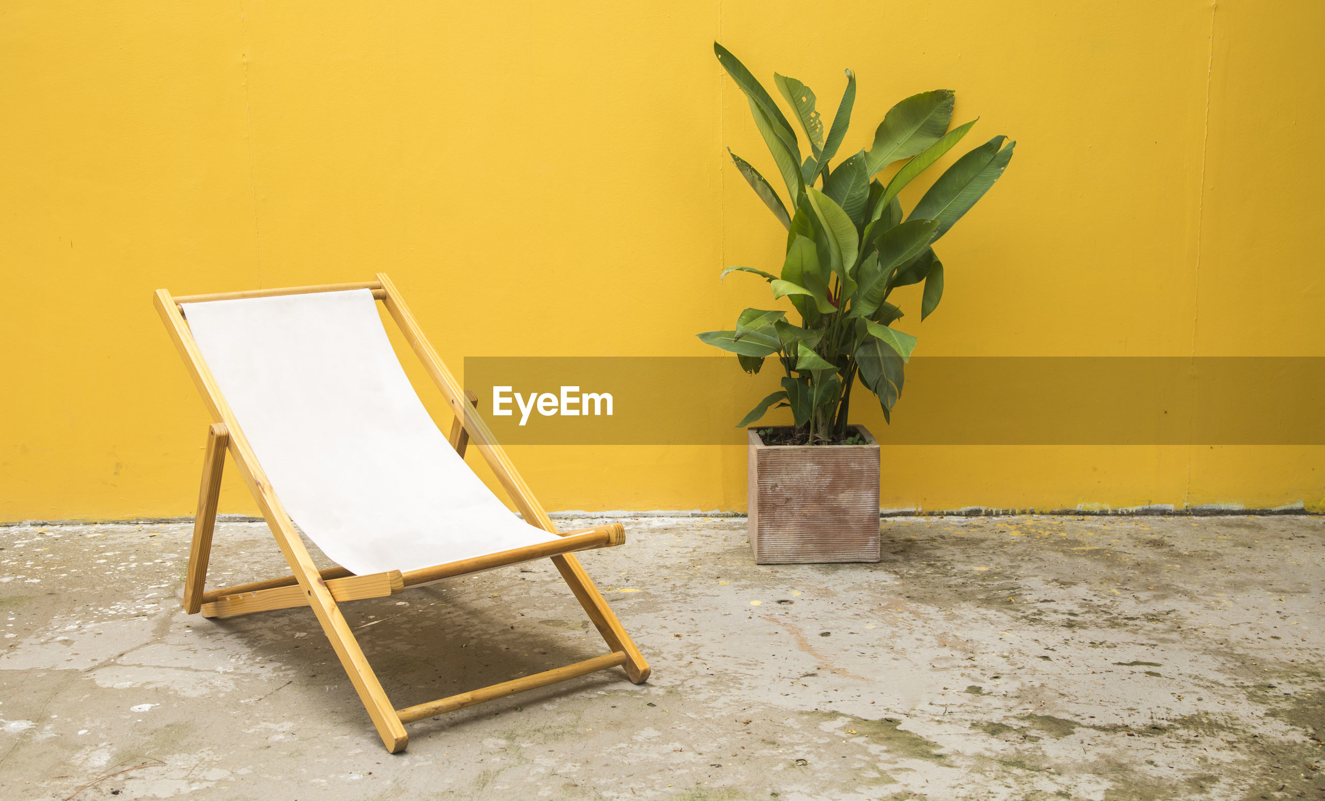 EMPTY CHAIRS AND YELLOW TABLE AGAINST WALL