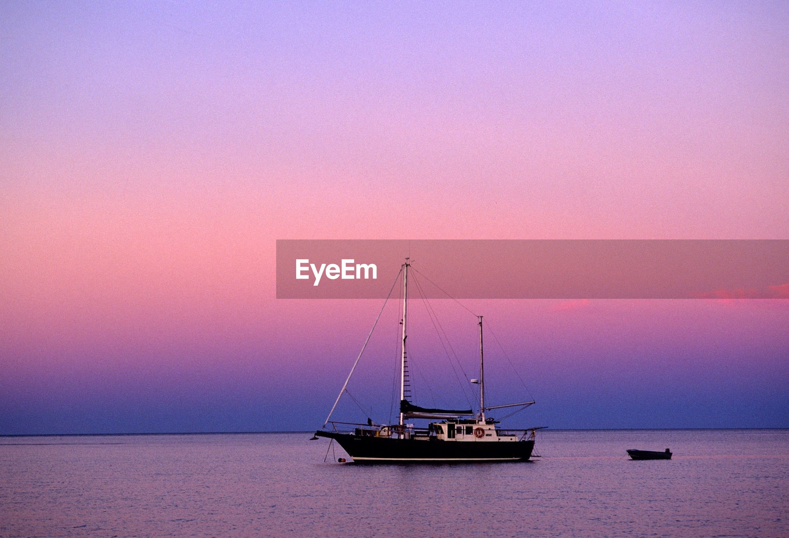 Sailboat in sea against romantic sky at sunset
