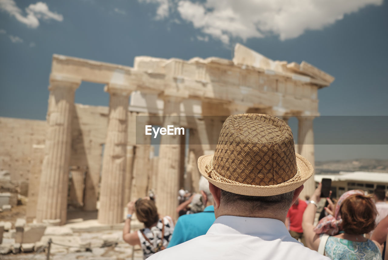 hat, architecture, real people, rear view, lifestyles, headshot, adult, clothing, built structure, men, portrait, women, travel destinations, people, tourism, leisure activity, focus on foreground, group of people, tourist, day, outdoors