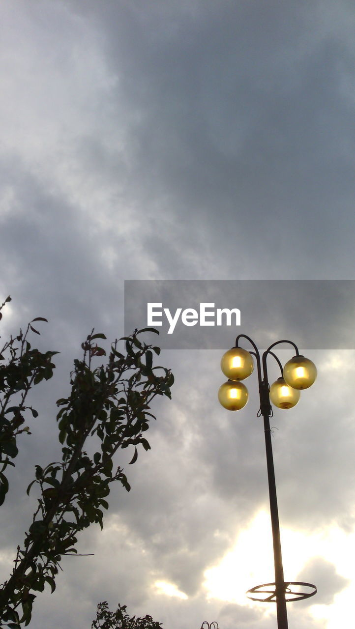 Street light against cloudy sky