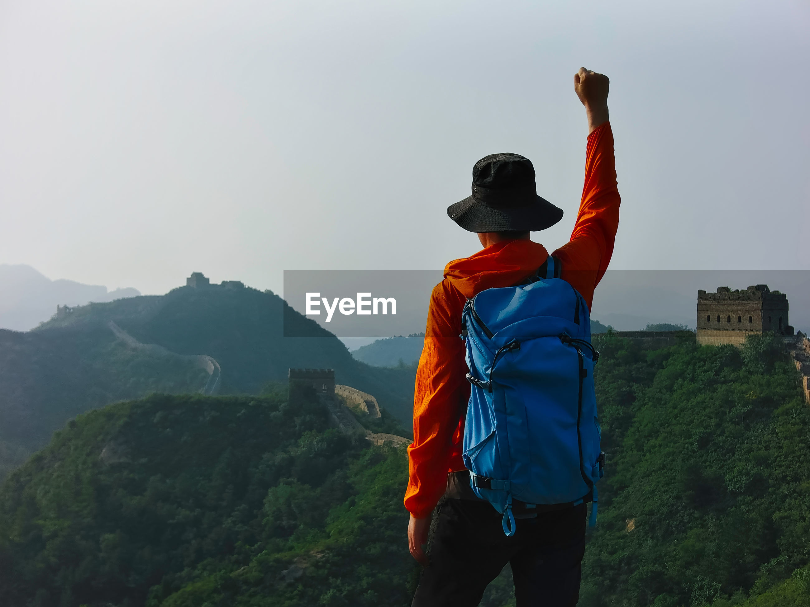 Male hiker with hand raised standing against great wall of china