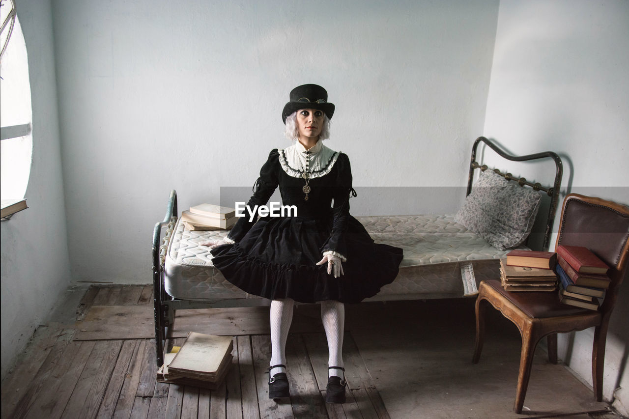 Portrait of woman wearing costume while sitting on bed at home