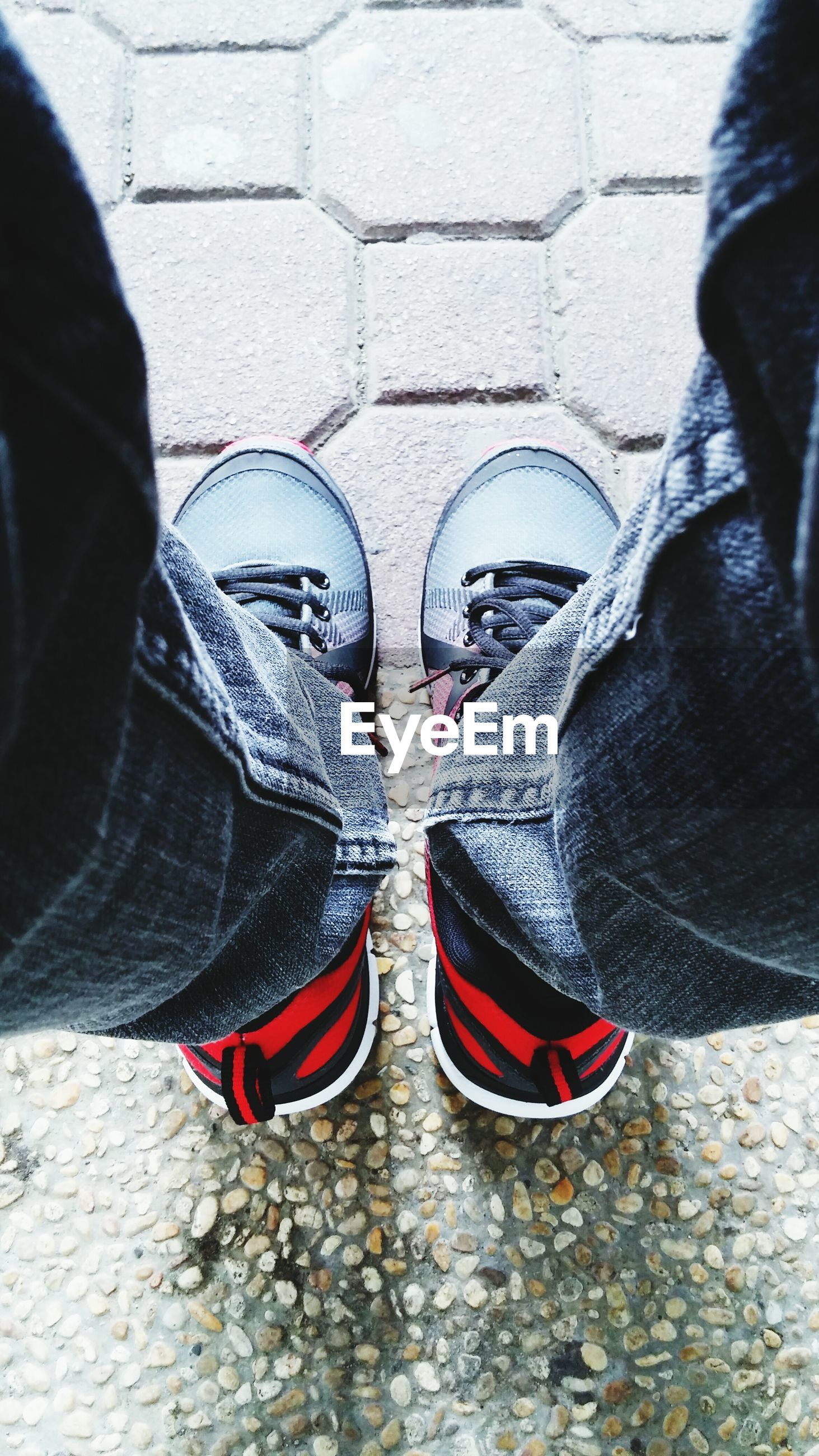 low section, shoe, person, standing, footwear, jeans, lifestyles, men, street, canvas shoe, casual clothing, human foot, pair, red, high angle view, unrecognizable person