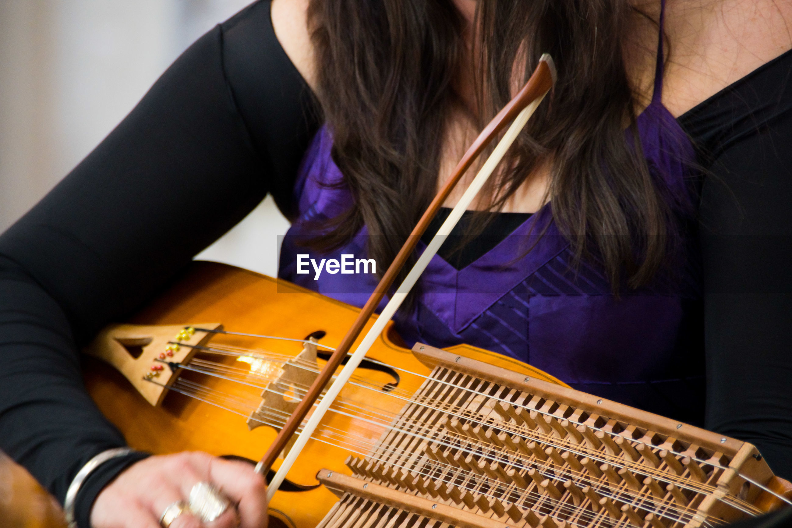 Midsection of woman playing string instrument