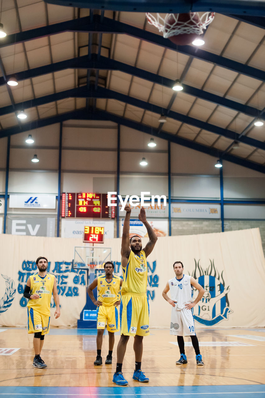arms raised, medium group of people, indoors, full length, sport, basketball - sport, sports uniform, boys, real people, basketball player, competition, team sport, togetherness, childhood, sports team, court, soccer uniform, day, people