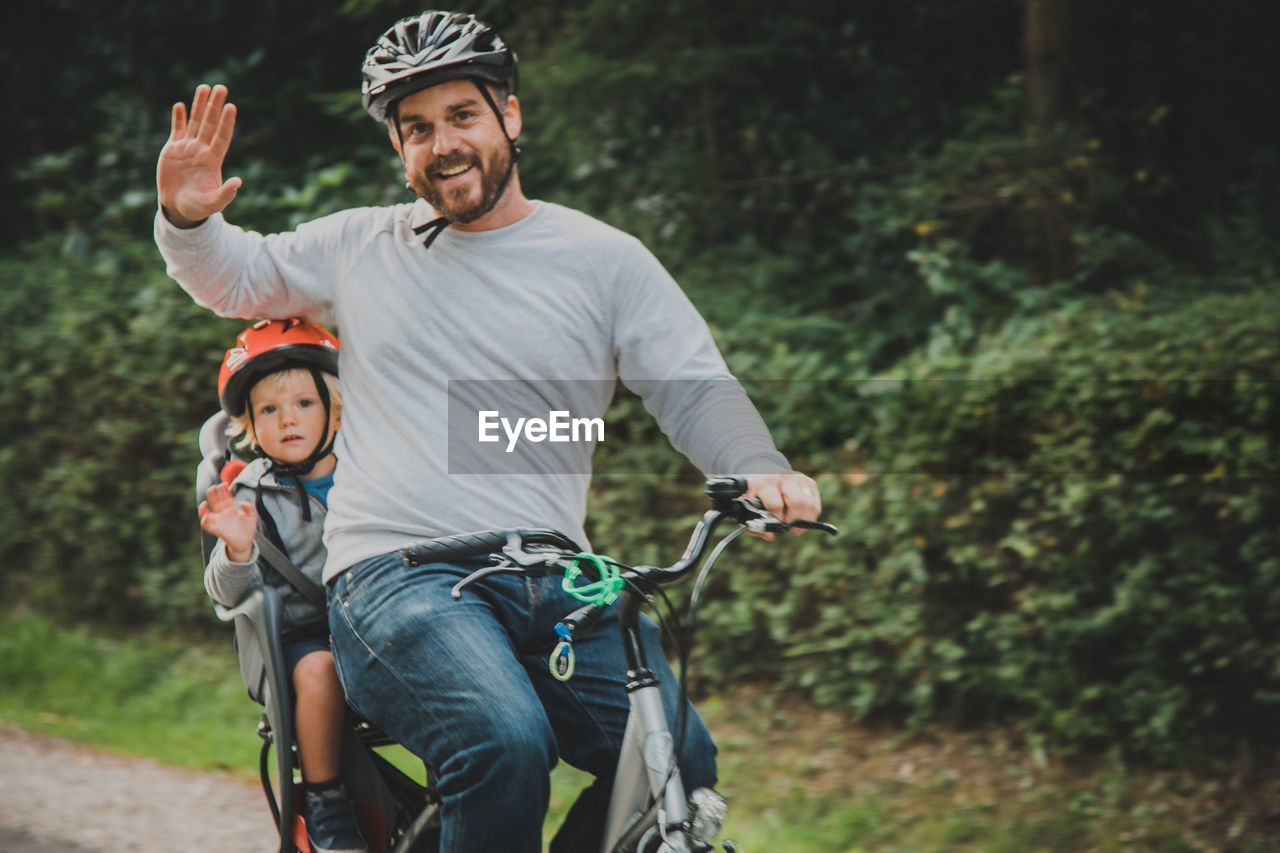 Portrait of father and son waving by cycling against plants