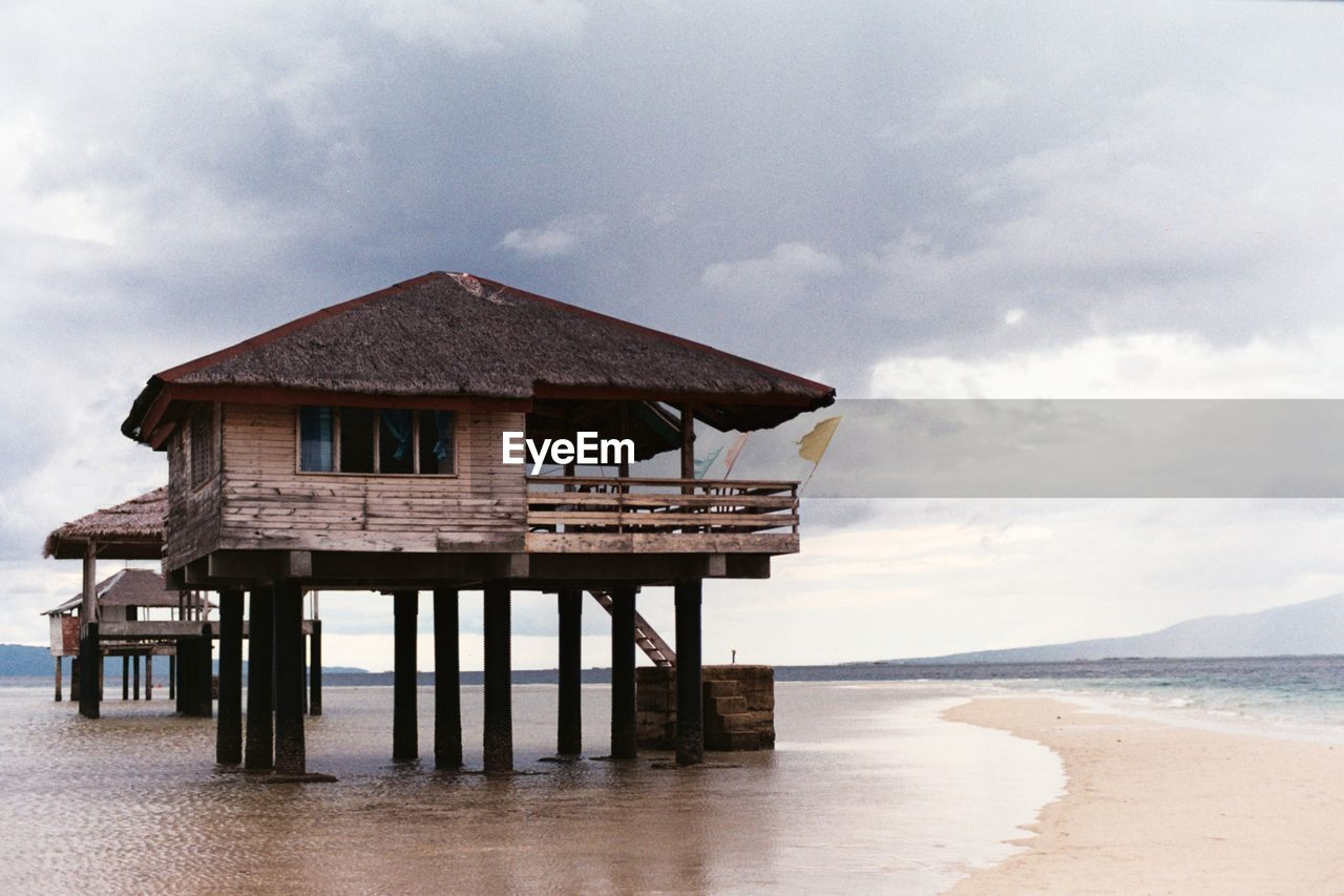 STILT HOUSE ON BEACH AGAINST SKY