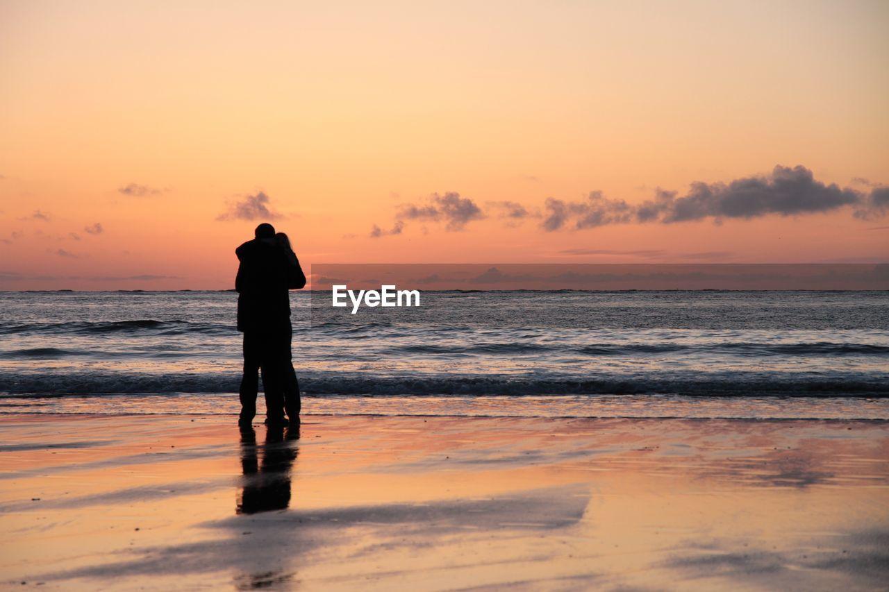 Couple On Beach Against Sunset Sky
