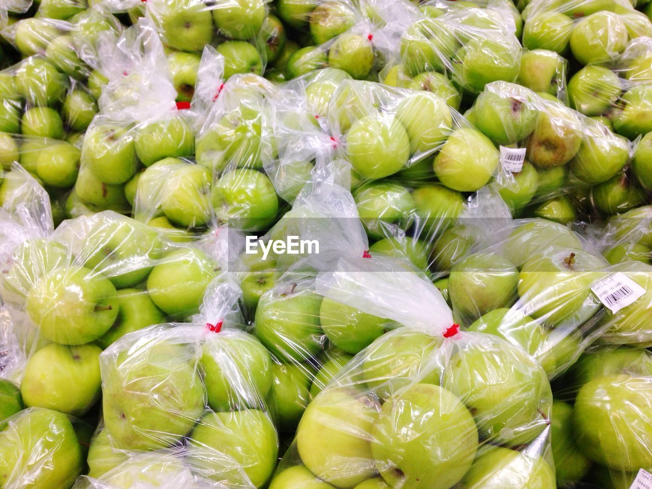 Full Frame Shot Of Granny Smith Apples Packed In Plastic At Market For Sale