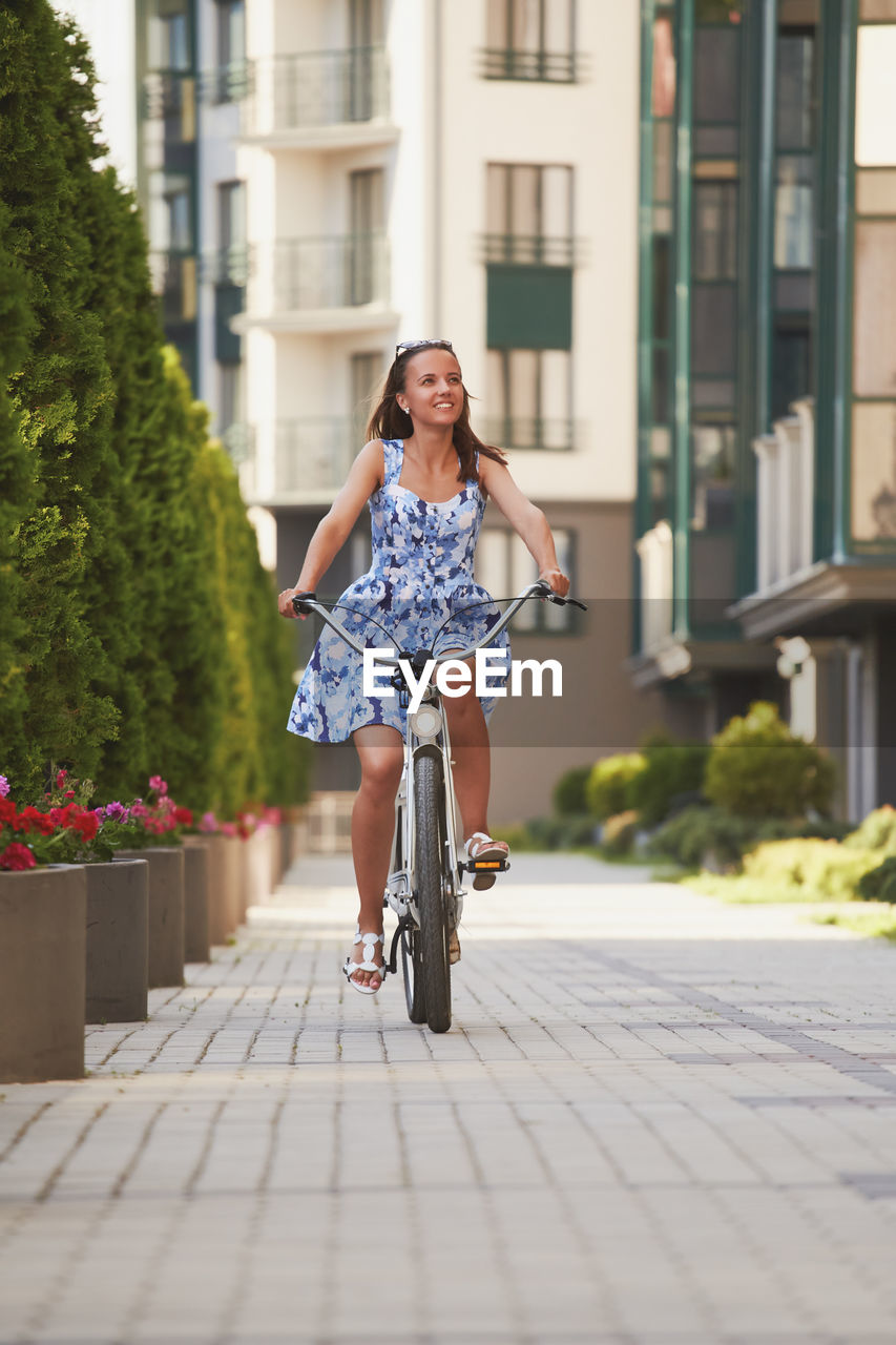 Full length of woman riding bicycle on city