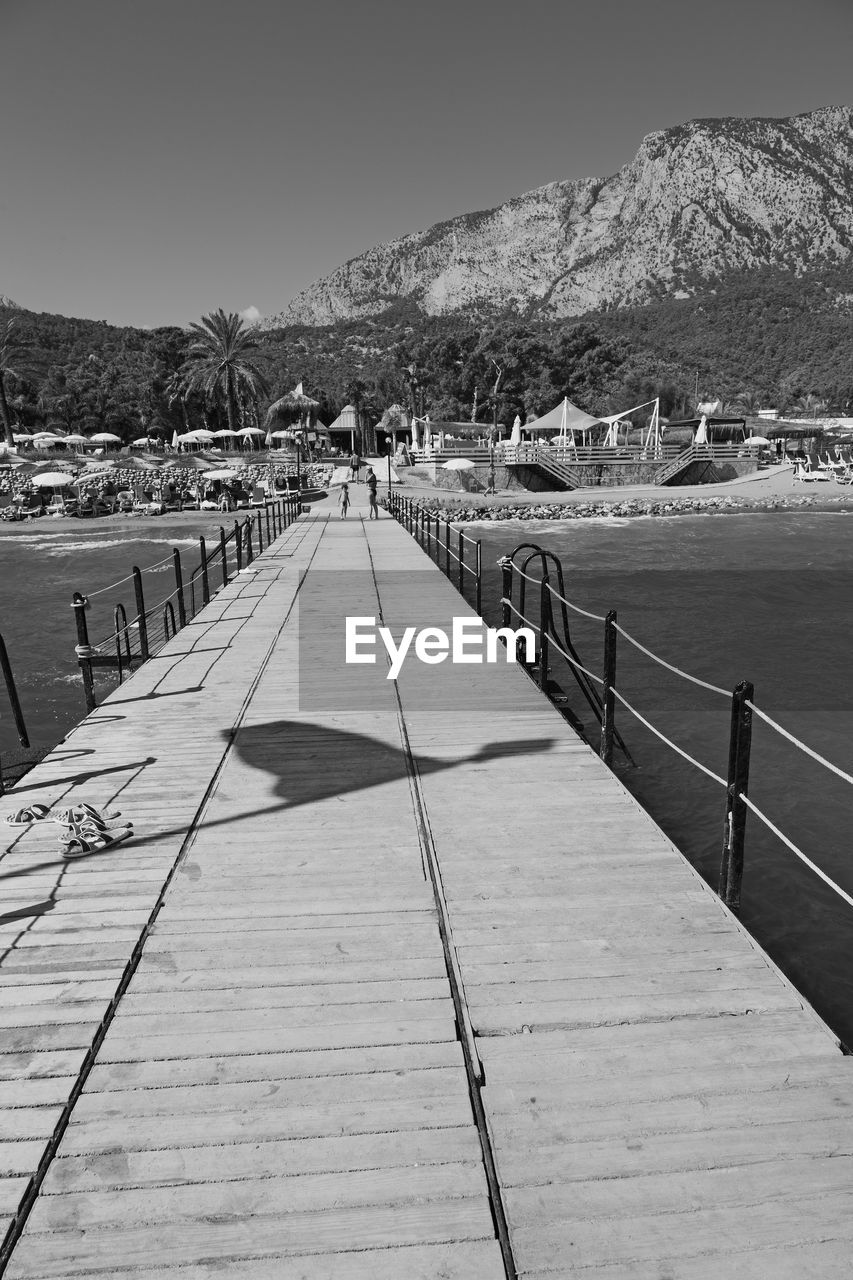 mountain, sky, water, nature, the way forward, incidental people, architecture, day, sea, direction, pier, built structure, land, beauty in nature, sunlight, outdoors, clear sky, footpath, railing, diminishing perspective
