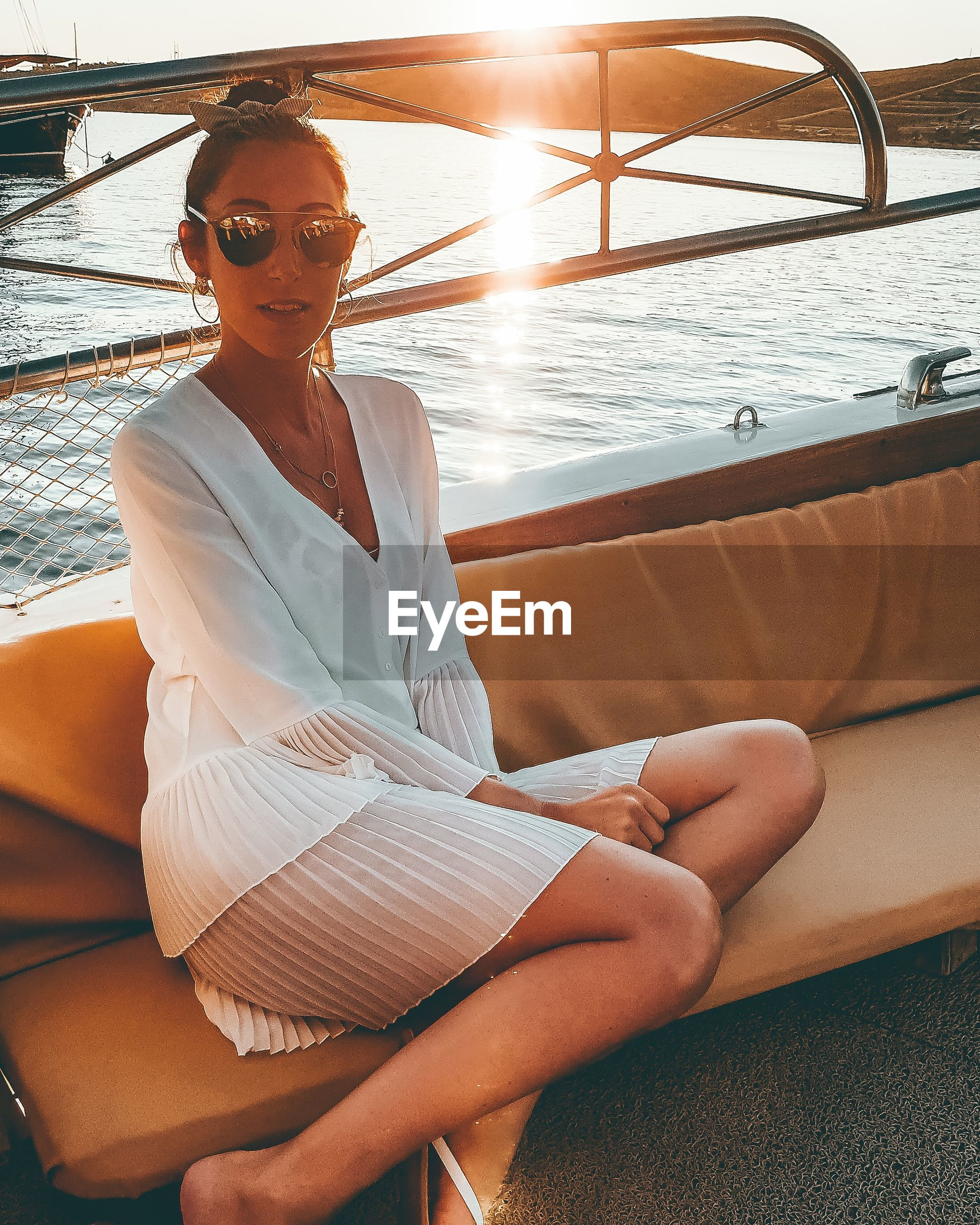 Portrait of young woman sitting on boat in sea during sunset
