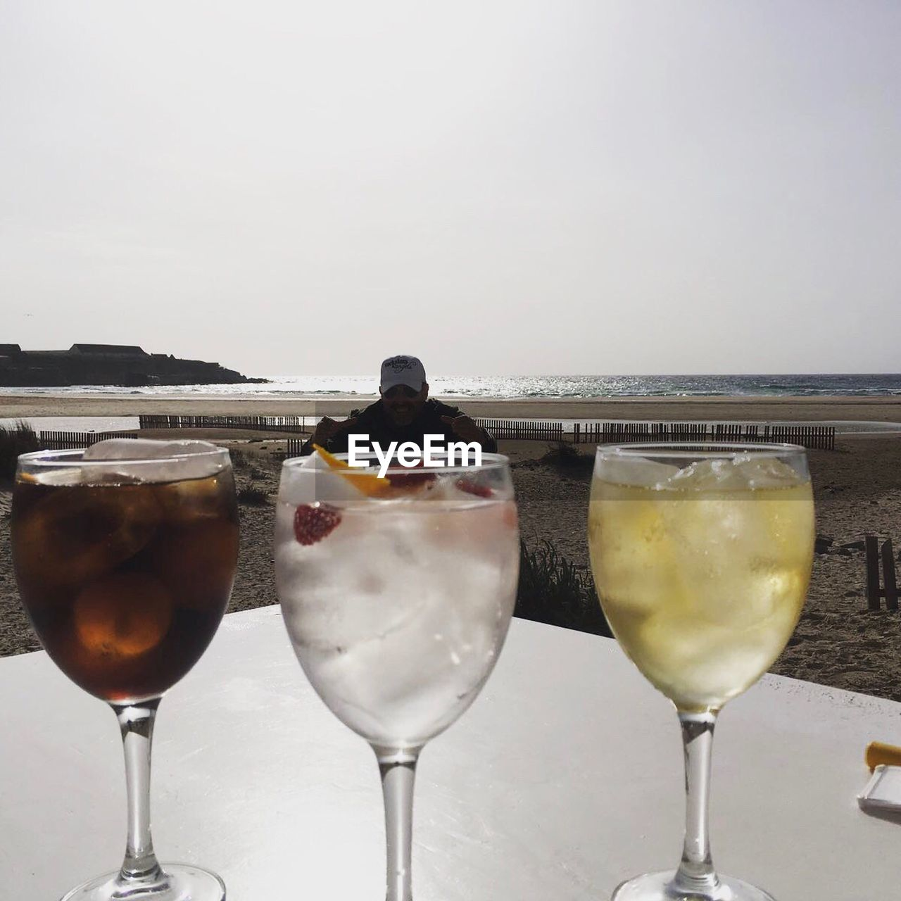 alcohol, food and drink, drink, drinking glass, refreshment, wineglass, wine, cocktail, sea, horizon over water, table, beach, close-up, freshness, outdoors, sky, clear sky, tropical drink, no people, white background, day, food
