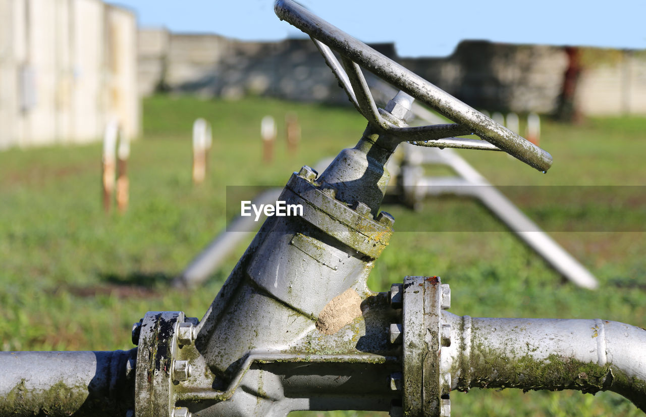 metal, outdoors, day, no people, focus on foreground, rusty, green color, grass, field, close-up, irrigation equipment, water