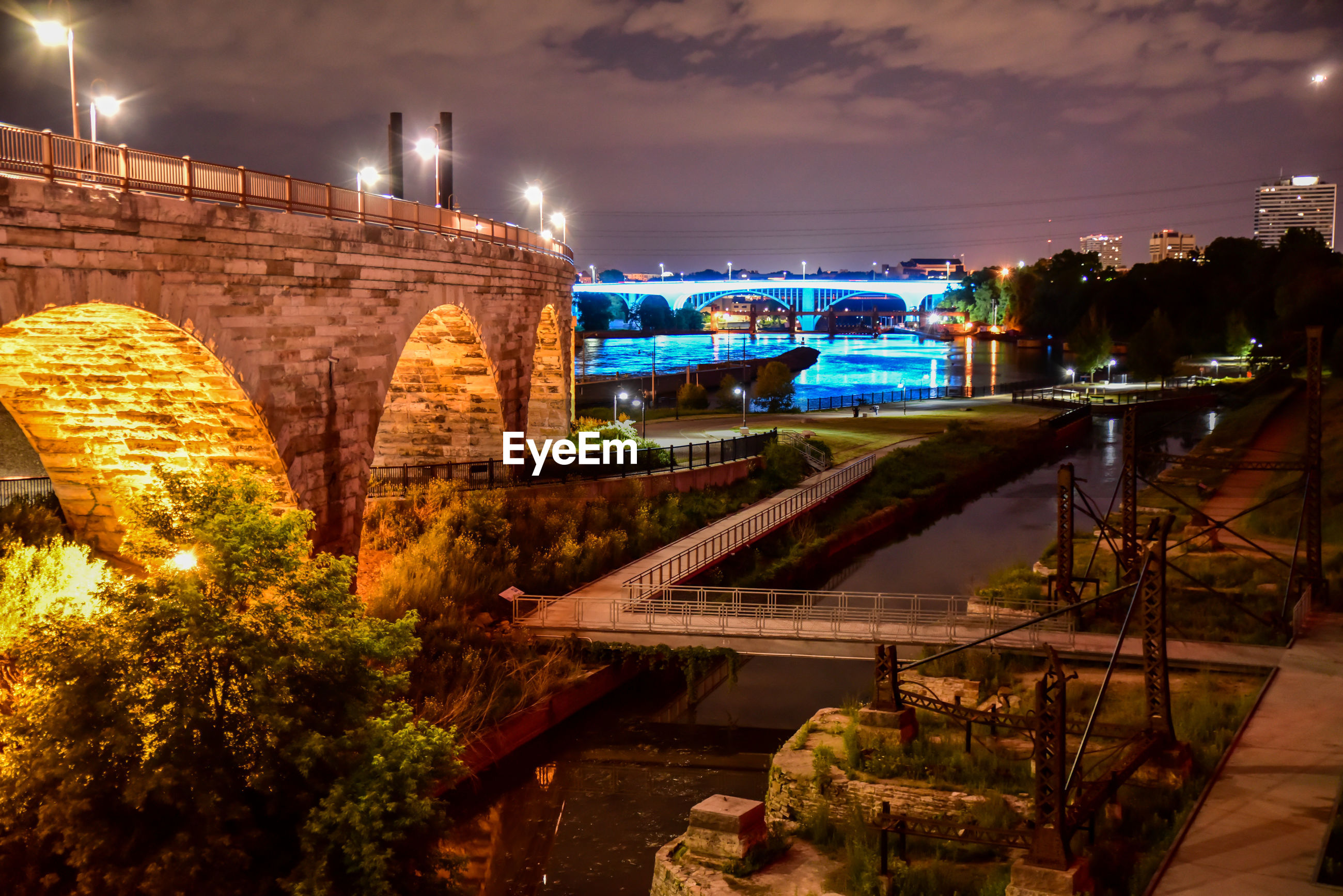 Bridge over river in city against sky at night