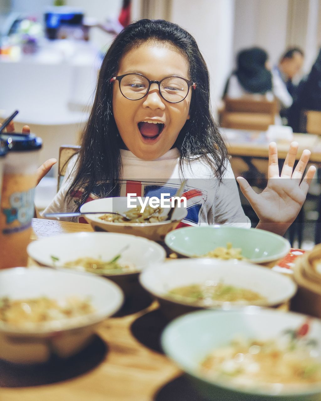 Surprised girl looking at meal on table in restaurant