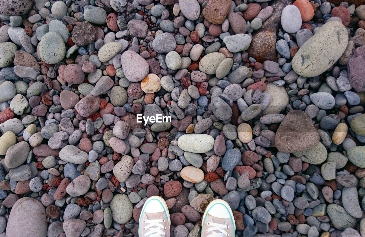 Low section of person wearing shoes on pebbles