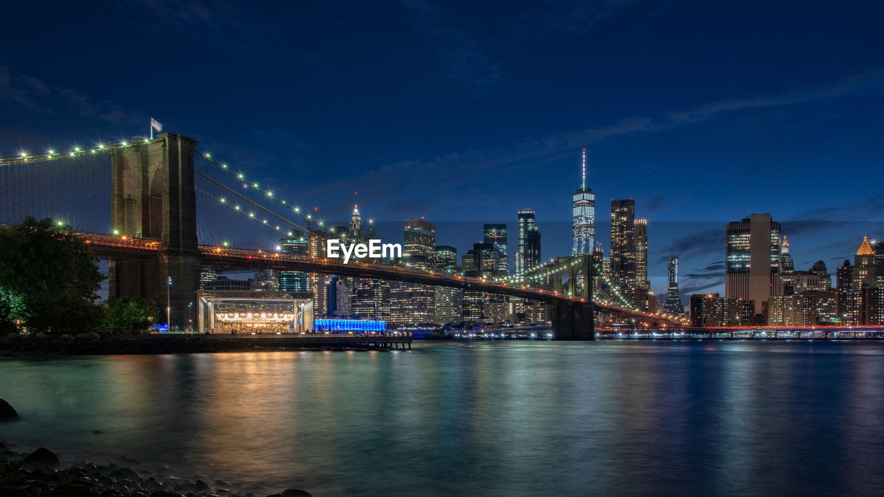 architecture, built structure, water, city, building exterior, bridge, river, sky, night, illuminated, connection, bridge - man made structure, transportation, waterfront, office building exterior, nature, skyscraper, travel destinations, no people, tall - high, cityscape, outdoors, modern, bay