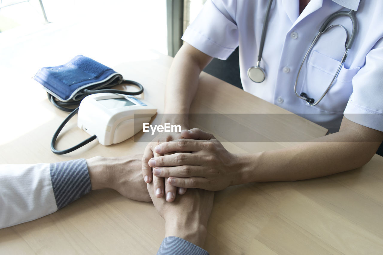 Midsection of doctor consoling patient on table