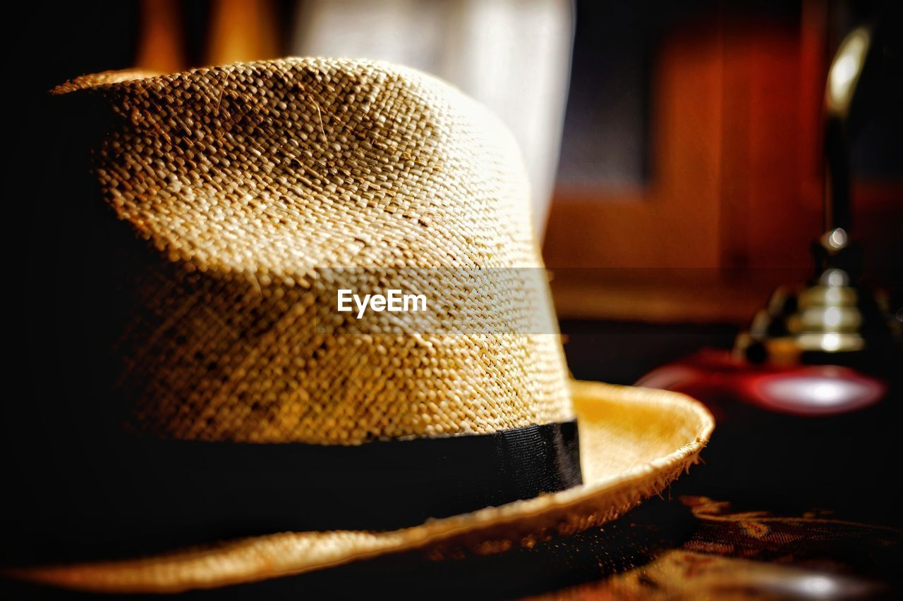 hat, clothing, close-up, focus on foreground, indoors, still life, table, fashion, no people, selective focus, headwear, personal accessory, elegance, straw hat, protection, textile, bag, security, gold colored, luxury, leather