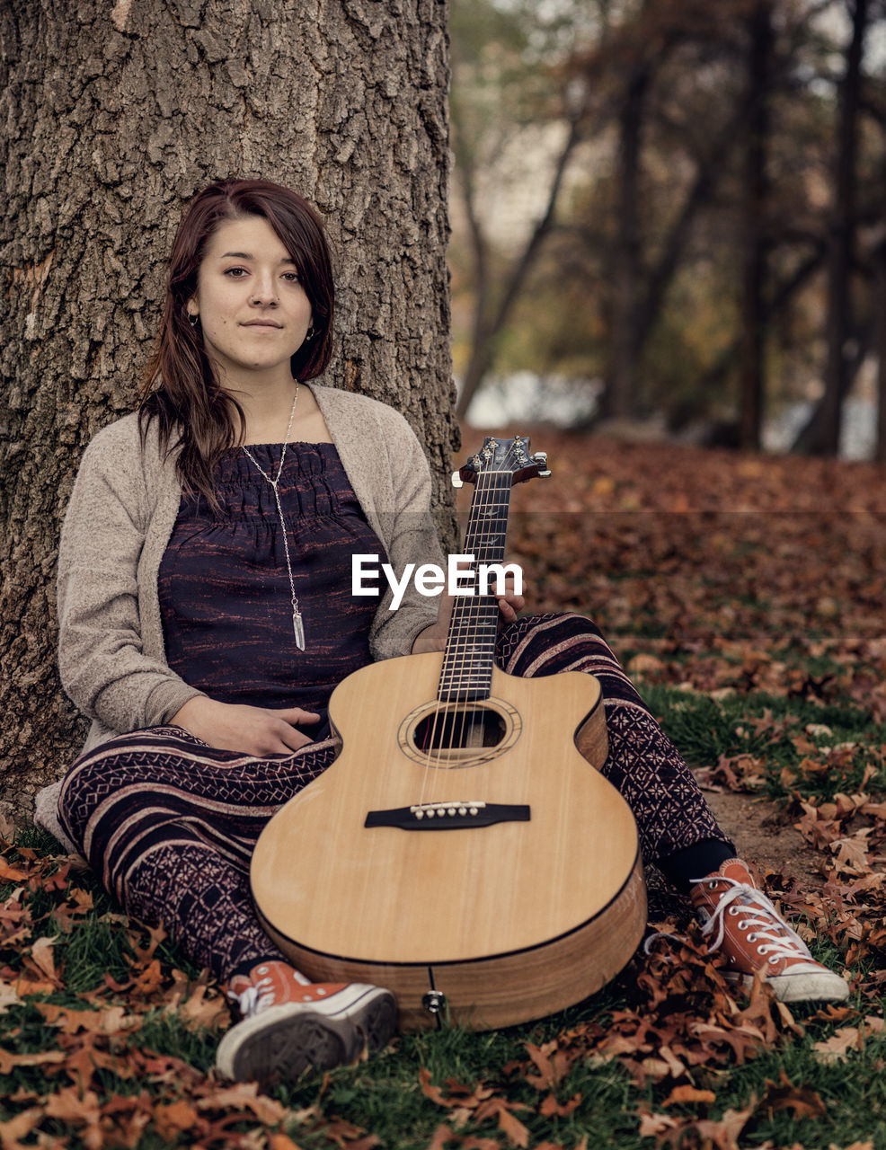 Portrait of young woman holding guitar sitting against tree trunk
