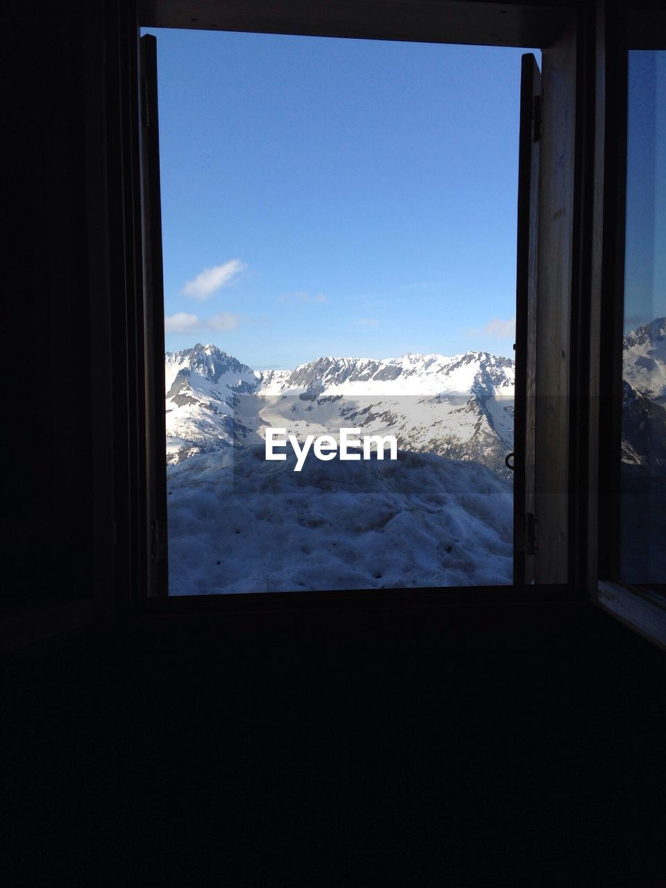 Snow Covered Mountains Against Sky Seen Through Home Window