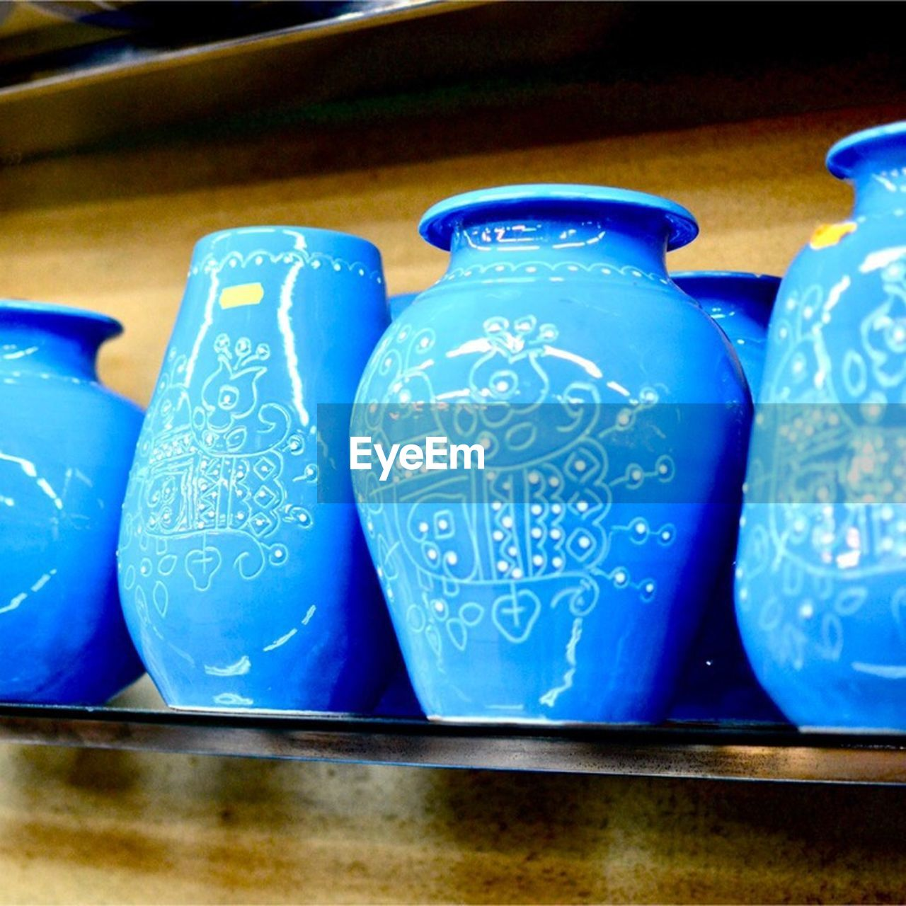 blue, indoors, no people, still life, close-up, table, container, ceramics, art and craft, side by side, arrangement, pattern, pottery, group of objects, focus on foreground, design, business, creativity, in a row, vase, pitcher - jug