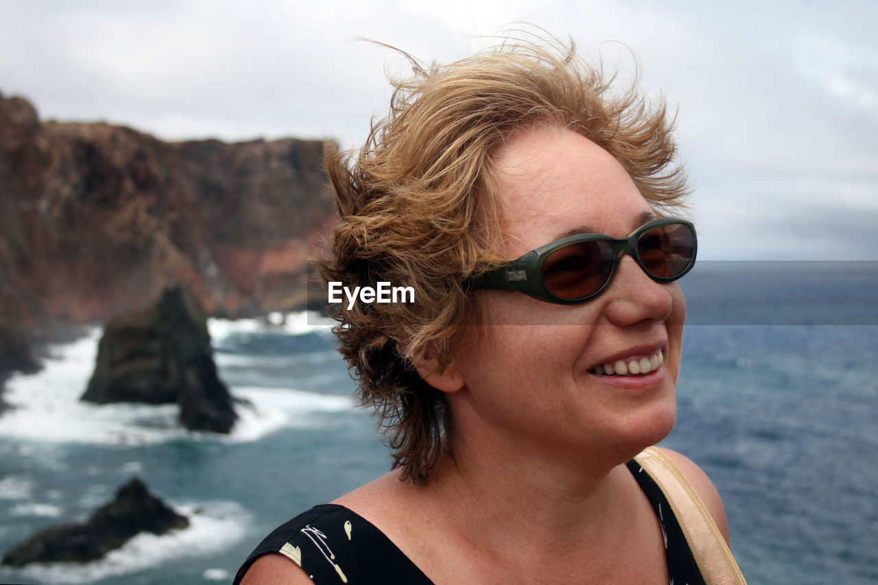 Middle-aged woman enjoying wind on the sea coast. woman is wearing sunglesses. mental health concept
