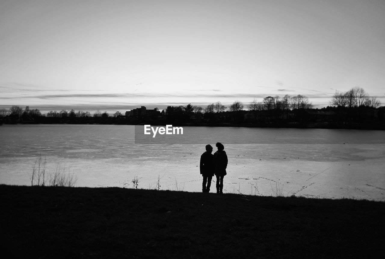 togetherness, two people, nature, lake, silhouette, tranquil scene, family, tranquility, sky, real people, full length, outdoors, sunset, beauty in nature, landscape, scenics, friendship, clear sky, men, bonding, water, day, mammal, people