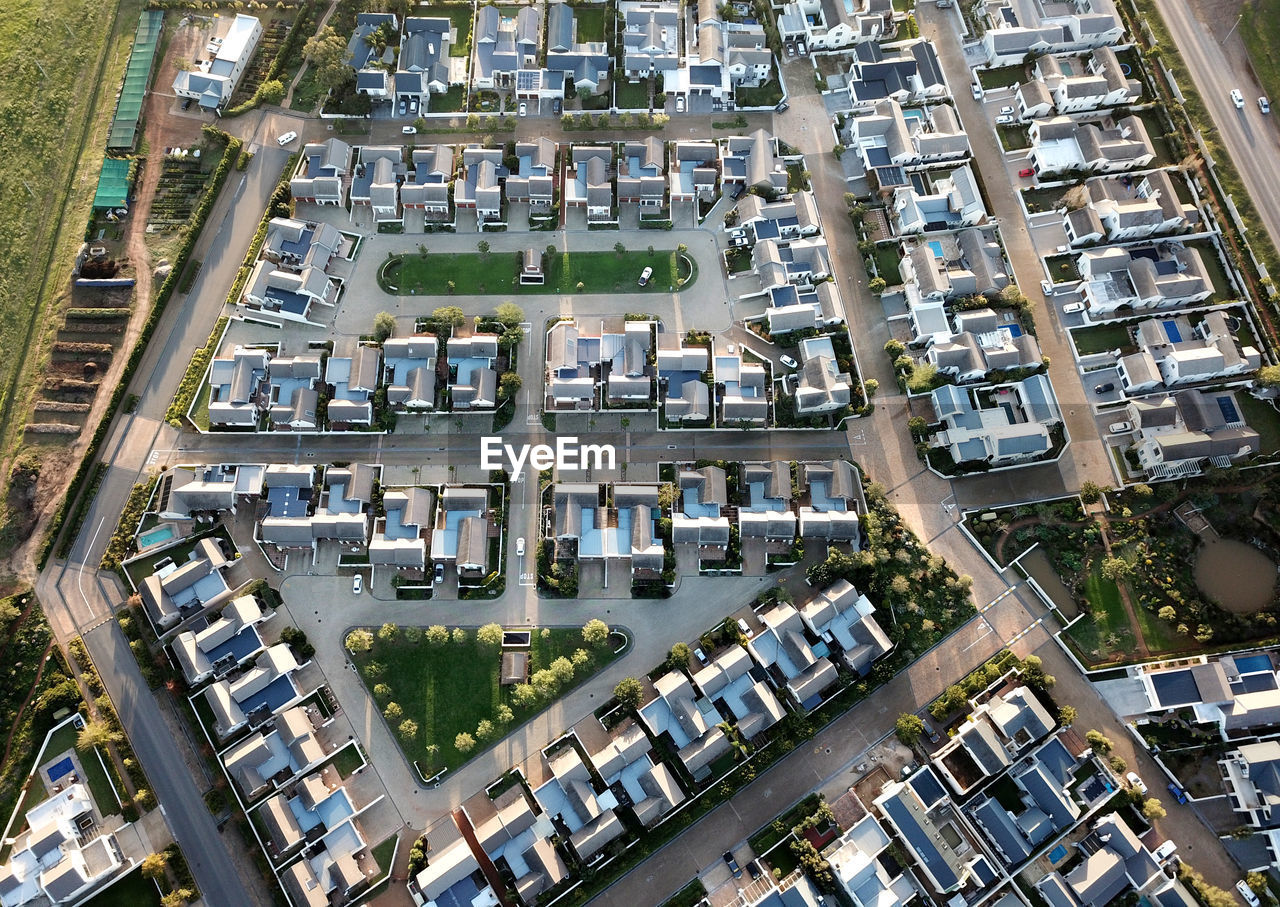 building exterior, architecture, built structure, city, high angle view, aerial view, transportation, residential district, day, car, road, motor vehicle, street, mode of transportation, building, no people, outdoors, roof, land vehicle, house, cityscape, apartment
