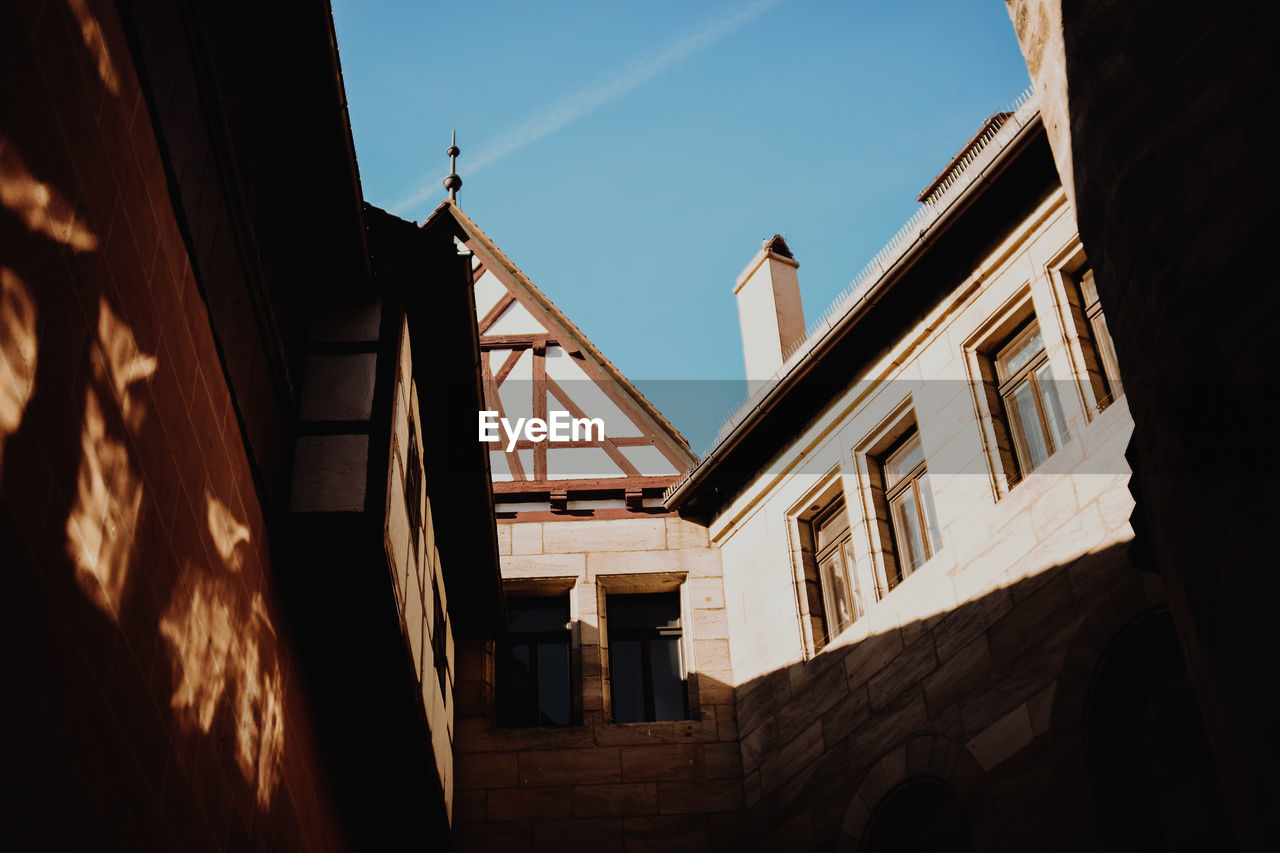 architecture, built structure, building exterior, building, low angle view, sky, day, window, residential district, house, no people, nature, outdoors, sunlight, city, old, wall, shadow, communication, wall - building feature