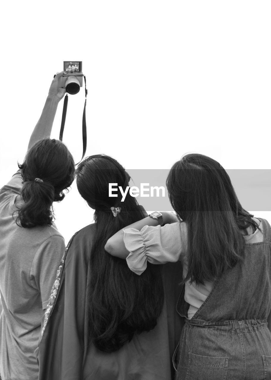 Rear view of female friends taking selfie