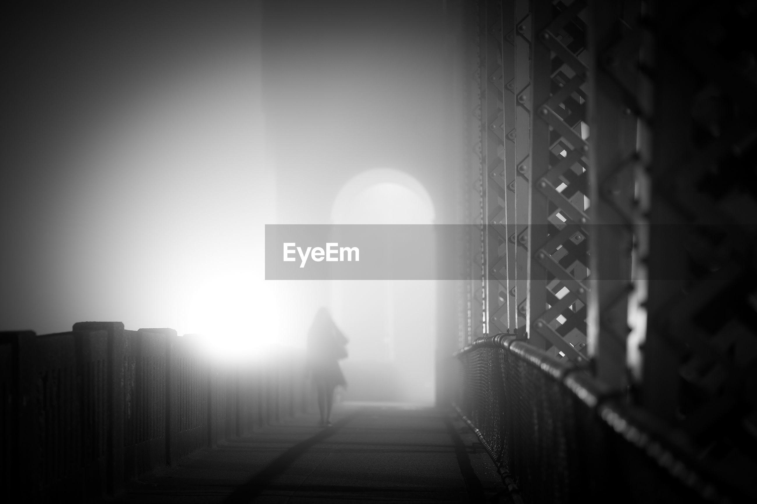 Silhouette woman walking on bridge during foggy weather