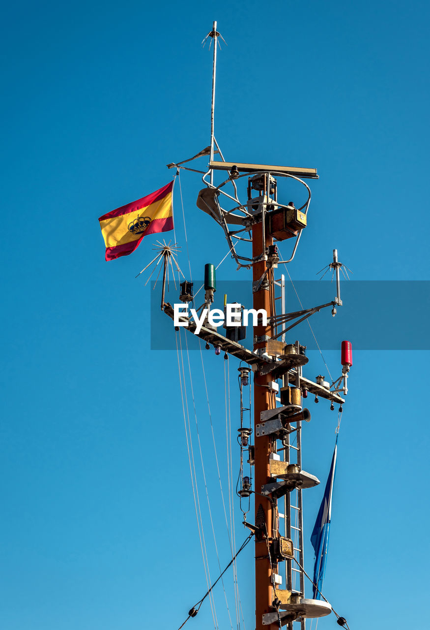 Low angle view of spanish flag on mast against clear blue sky