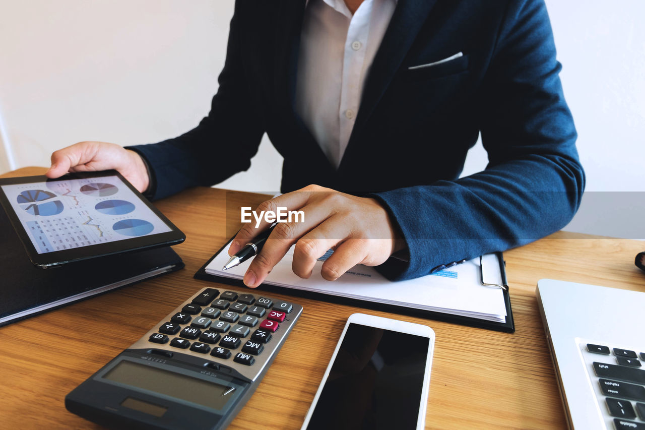 technology, business, calculator, table, one person, real people, indoors, businessman, business person, computer, adult, midsection, connection, wireless technology, men, communication, occupation, furniture, males, hand, calculating, keyboard