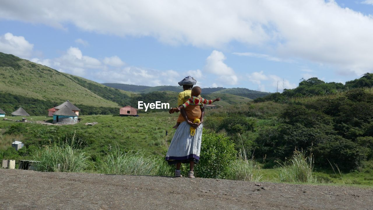 Rear View Of Mother Carrying Baby Boy While Standing Against Mountains