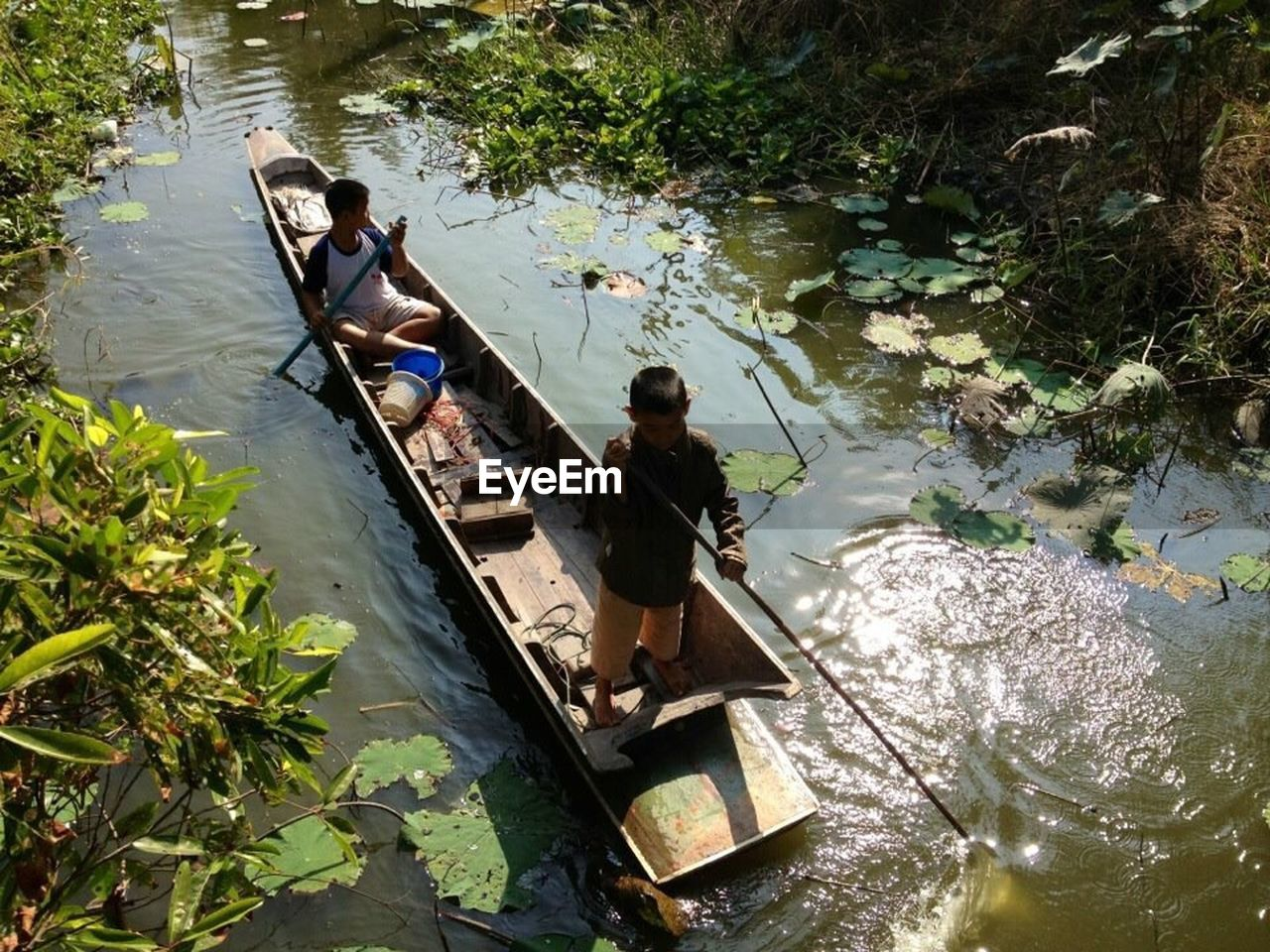 real people, high angle view, water, day, full length, nature, outdoors, two people, oar, nautical vessel, lifestyles, transportation, boys, leisure activity, sitting, men, beauty in nature, tree, gondola - traditional boat, adult, people