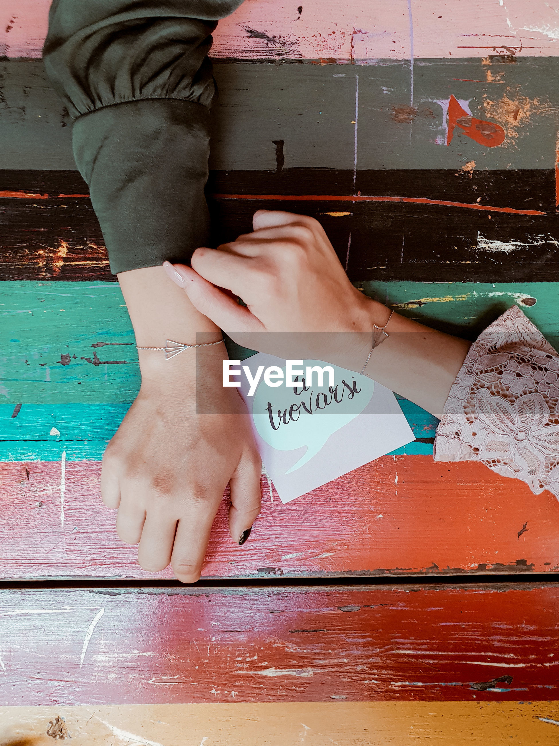 Directly above shot of women hands with message on table