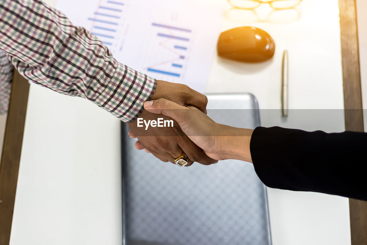 Cropped hands of colleagues handshaking over office desk