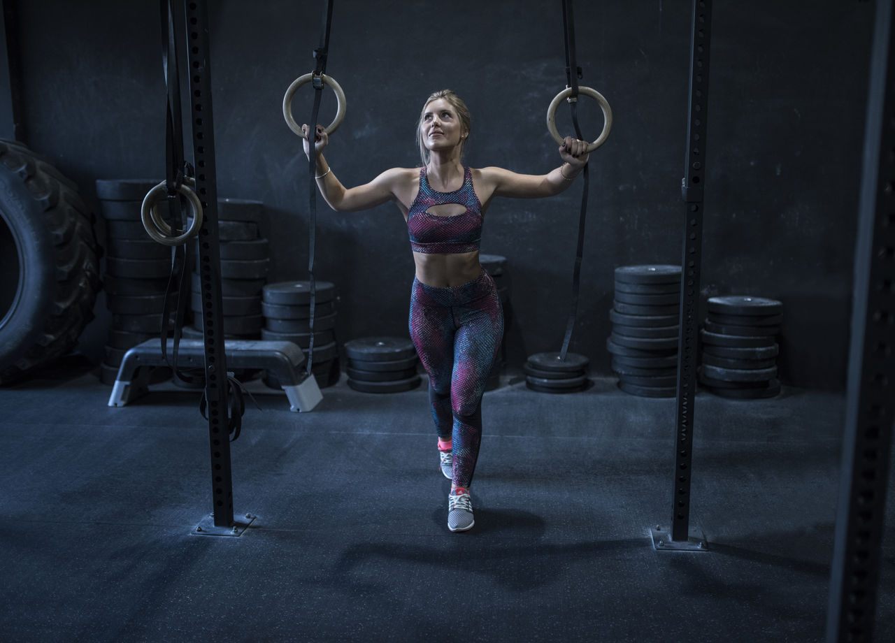 Full length of young woman holding gymnastic rings while exercising in gym