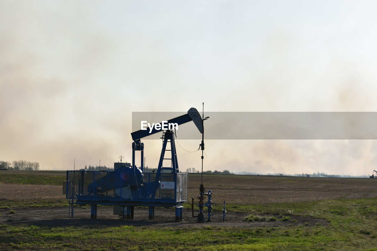 sky, land, field, cloud - sky, industry, fuel and power generation, nature, oil well, oil pump, environment, oil industry, landscape, machinery, no people, equipment, oil field, outdoors, day, rural scene, sunset, industrial equipment