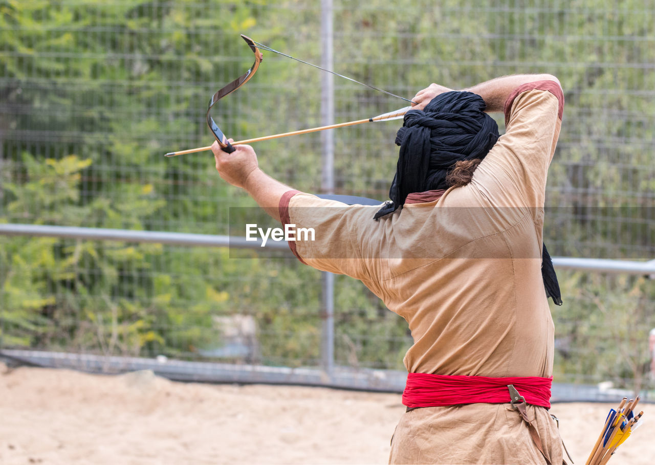 one person, day, holding, men, sport, real people, focus on foreground, lifestyles, nature, land, leisure activity, casual clothing, outdoors, adult, three quarter length, arrow - bow and arrow, motion, rear view, activity, hairstyle