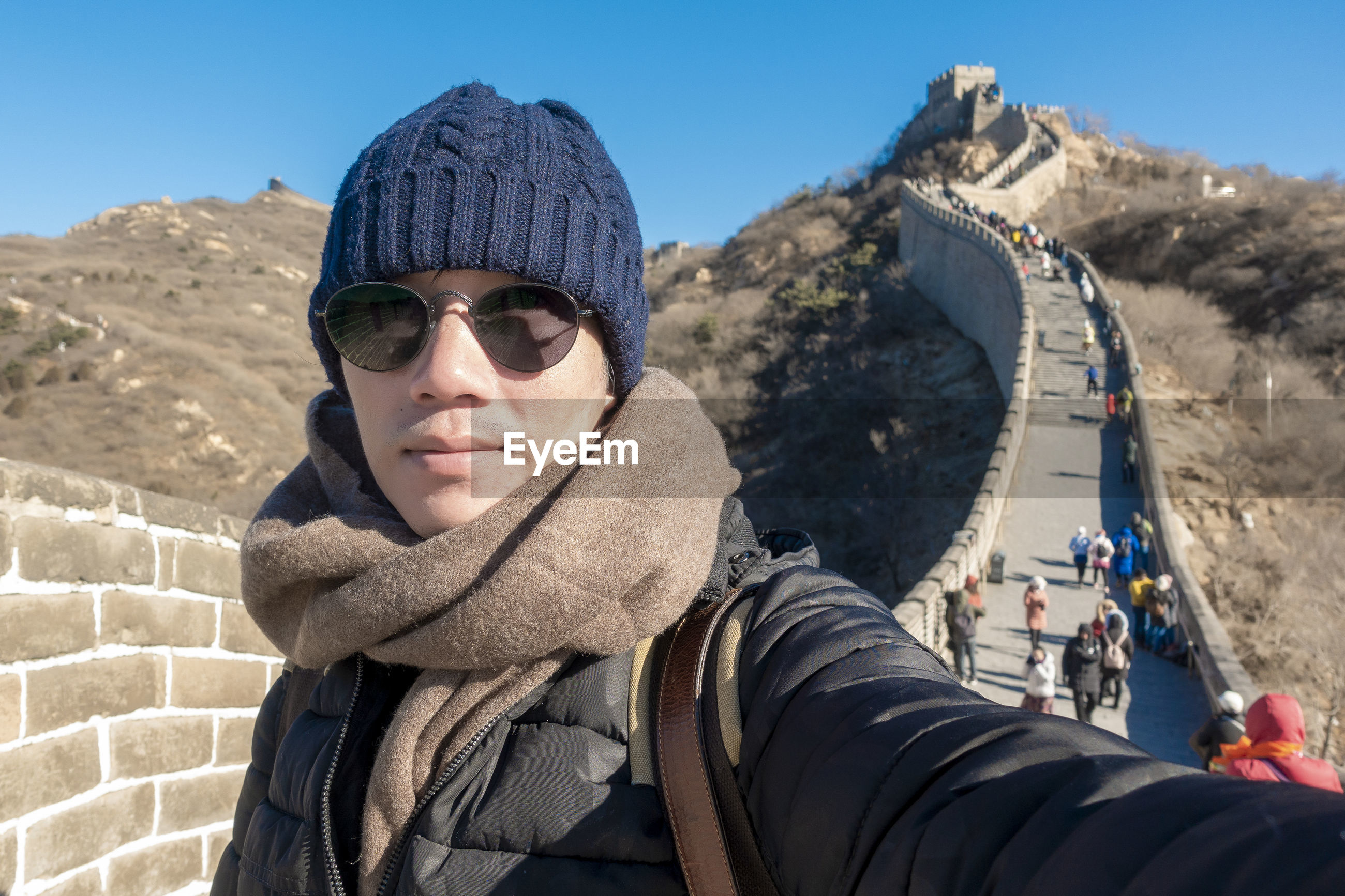 Portrait of man wearing sunglasses while standing at great wall of china
