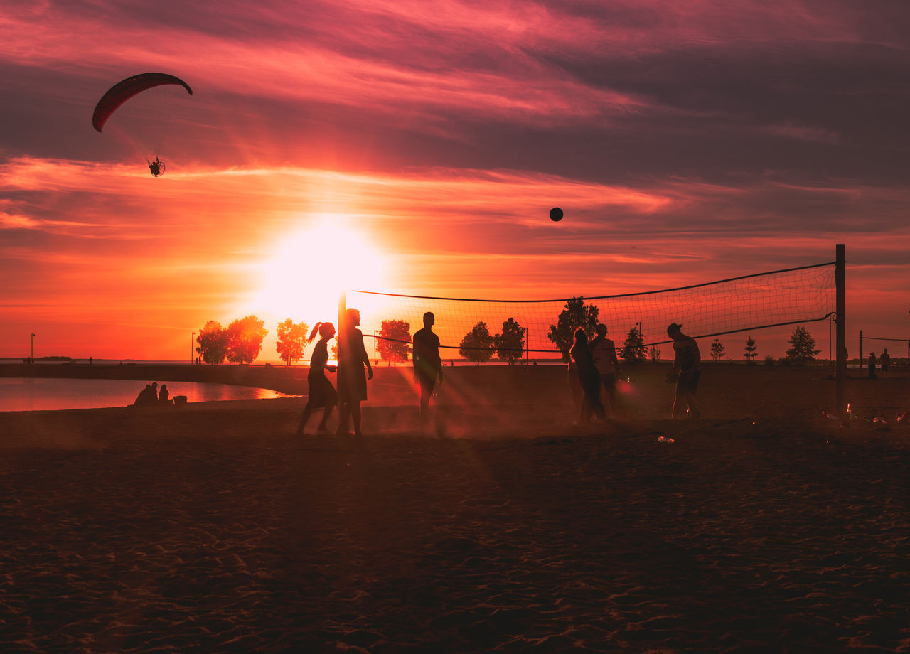 Silhouette friends playing beach volleyball against orange sky
