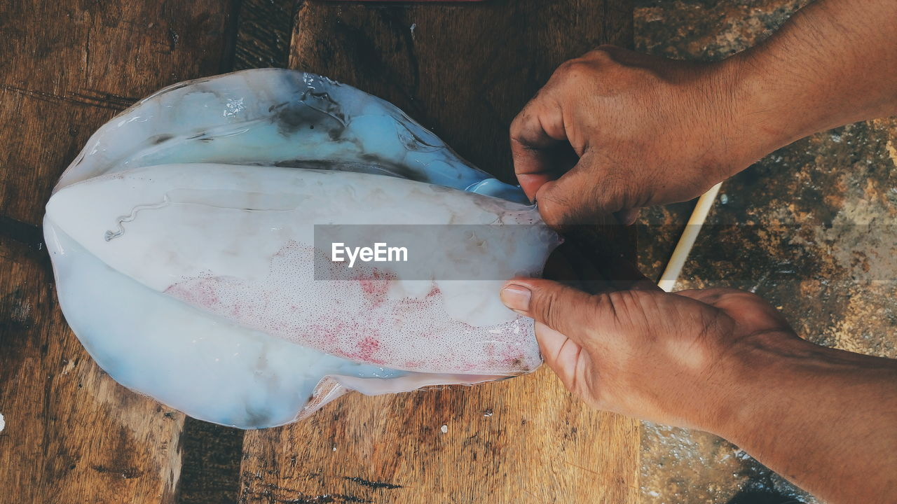 Close-Up Of Hands Preparing Seafood