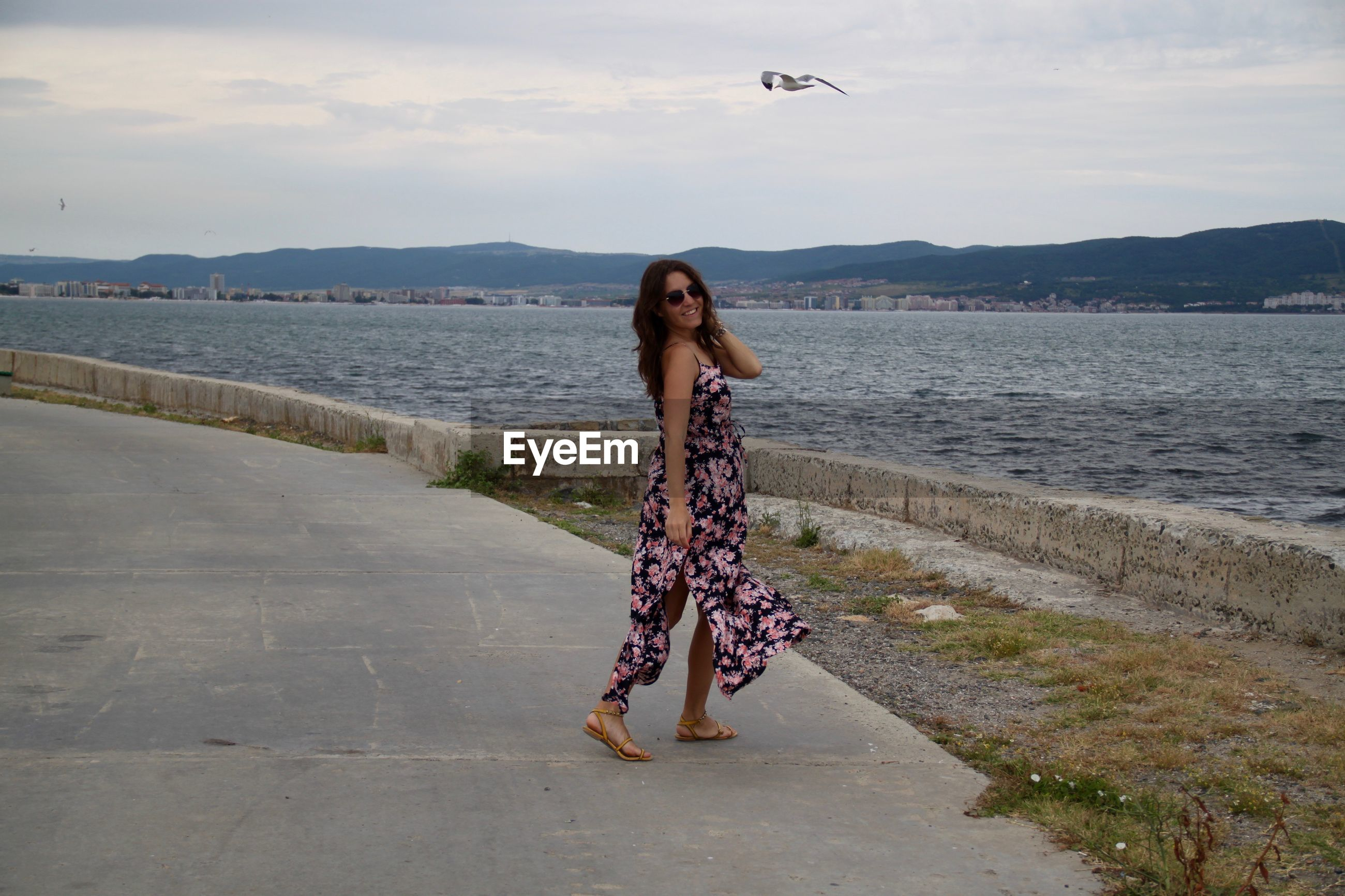Happy woman wearing floral dress walking on promenade by sea against sky