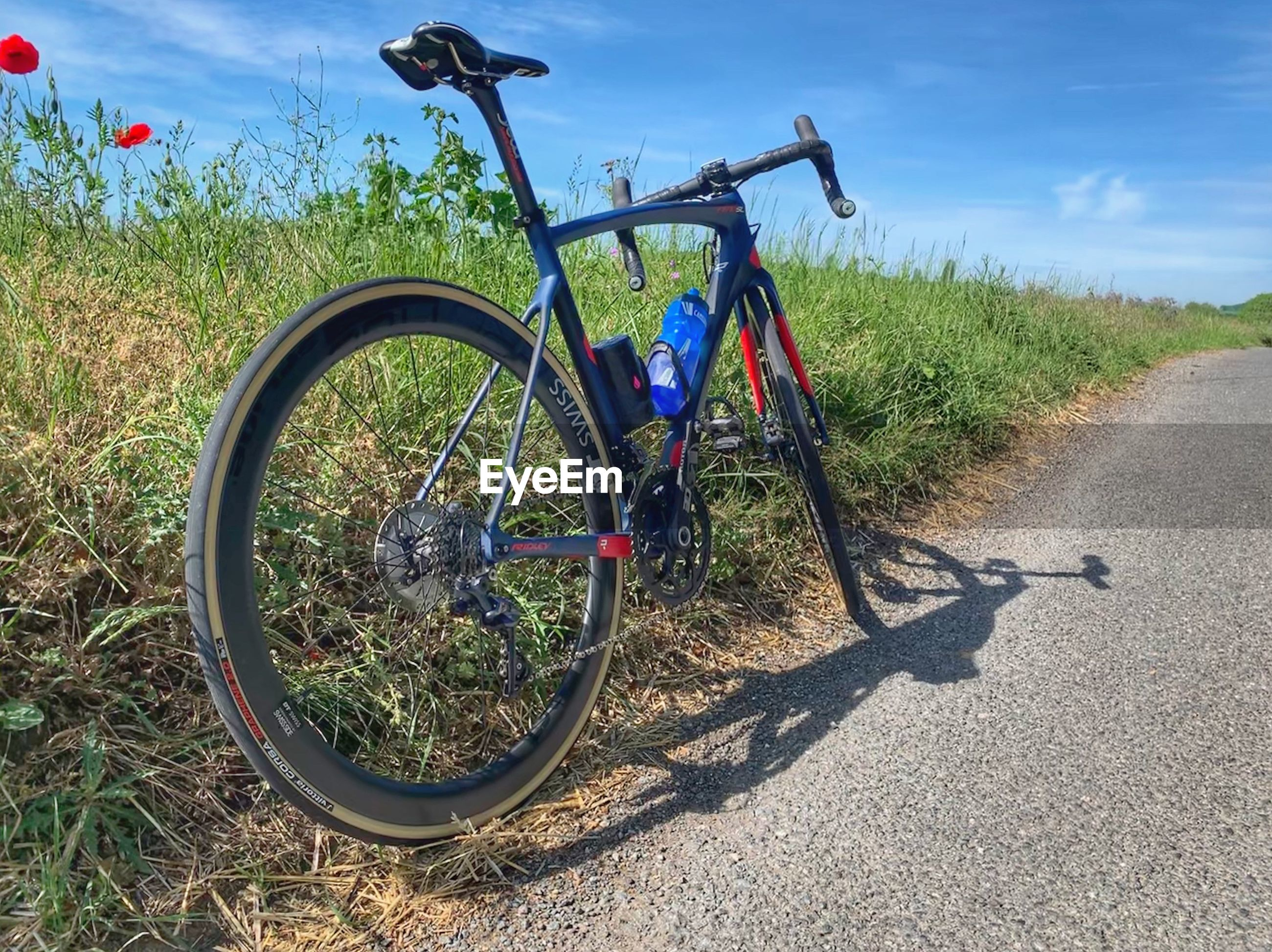 transportation, bicycle, land vehicle, mode of transportation, nature, plant, road, day, land, stationary, field, sunlight, grass, shadow, no people, sky, wheel, parking, outdoors, dirt, tire