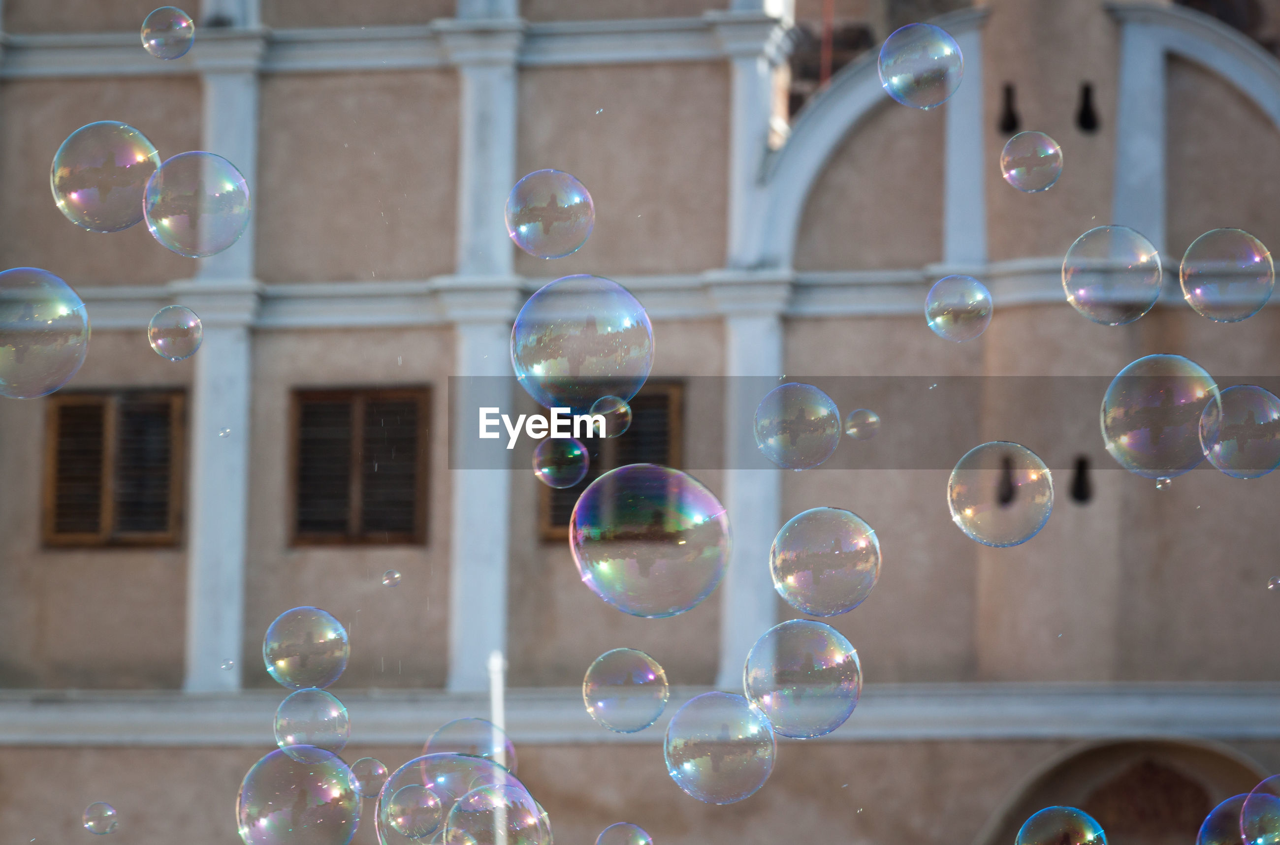 bubble, transparent, fragility, vulnerability, soap sud, no people, reflection, close-up, mid-air, focus on foreground, sphere, glass - material, nature, indoors, day, multi colored, shape, architecture, built structure